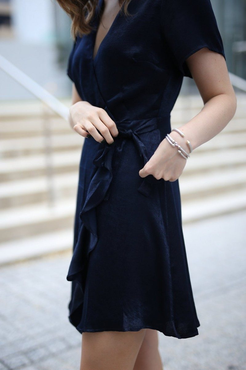 Style blogger Ashley Lane of Never Without Lipstick wears a navy wrap dress with block heels | holiday party dresses, affordable holiday party dresses, holiday party dresses under 50, holiday party outfit, holiday party outfit idea, wrap dress, navy dress, holiday party dress christmas, holiday party dress work, david yurman cuff, david yurman stack